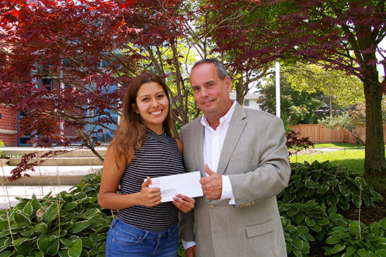 2017 President Jim Smith hands in the scholarship cheque to Natalia Pineda